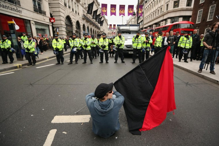 A protester sits on Piccadilly in front of a police line during a demonstration ahead of the G8 summit in Northern Ireland on June 11, 2013 in London, England. (Oli Scarff/Getty Images)