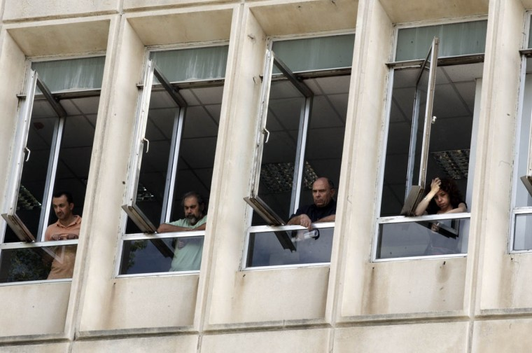 Workers look out from windows as they occupy the headquarters of the Greek public broadcaster ERT in Athens in Athens, Greece. Journalists have refused to leave the premises following the Greek government's announcement that the Hellanic Broadcasting Corporation (ERT) was to be disbanded, terminating television and radio broadcasts and dismissing all 2,500 journalists employed by the corporation, claiming that it was a 'haven of waste'. The station which began broadcasting in 1938 is continuing to air limited shortwave and internet broadcasts while the conservative led government has stated that it is planning to reopen as a smaller independent public broadcaster. (Milos Bicanski/Getty Images)