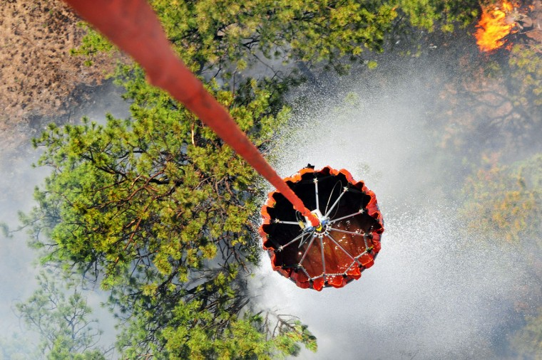 In this handout photo provided by the U.S. Army, Pilots and crewmembers of the United States Army release water onto the burning fires during their bambi bucket mission on June 12, 2013 in Black Forest, Colorado. The fire has burned over 15,000 acres, and has claimed 360 homes, forcing at least 38,000 people to evacuate. (Photo by Sgt. Jonathan C. Thibault/U.S. Army via Getty Images)