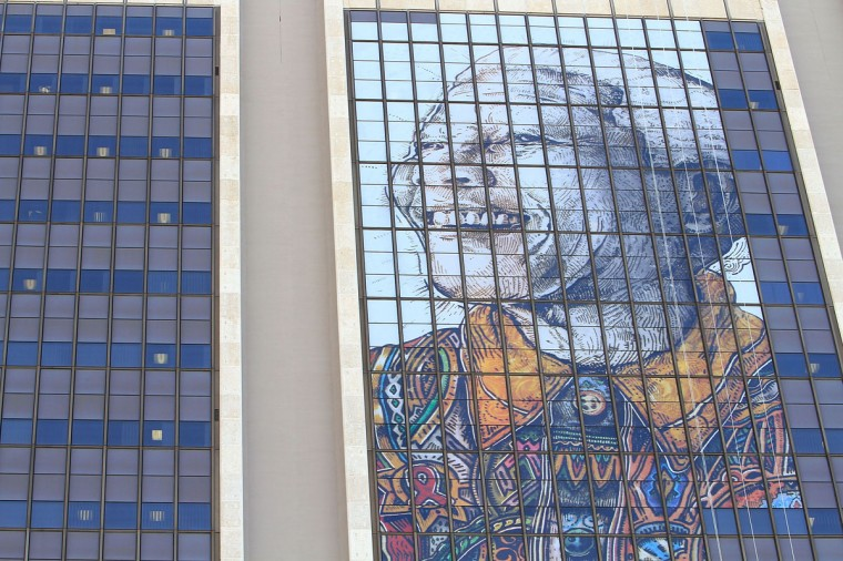 A Nelson Mandela murial hangs high at the Cape Town Civic Centre as part of the Nation wide prayers being held for the frail statesman in Cape Town, South Africa. The former South African President and leader of the anti-apartheid movement is spending a seventh day in a hospital and is reported to be responding better to treatment for a recurring lung infection. This is Mandela's fourth time in the hospital since December of 2012. (Michelly Rall/Getty Images)
