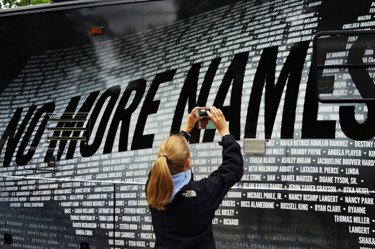 Lindsay Knauf takes a picture of a bus bearing some of the over 6,000 names of people killed by gun violence since the massacre in Newtown at a remembrance event on the six month anniversary of the massacre at Sandy Hook Elementary School in Newtown, Connecticut. A a 26-second moment of silence was observed to honor the 20 children and six adults who were killed at the school on Dec. 14. The event also included the reading of the names of over 6,000 people who have been killed by gun violence. The reading of names is expected to take 12 hours. (Spencer Platt/Getty Images)