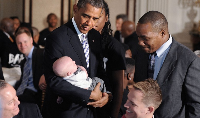 President Barack Obama holds a baby at a Father's Day luncheon to celebrate the importance of strong families and mentorship in the State Dining Room of the White House in Washington, D.C. Fathers and their children as well as students and leaders from the Becoming a Man (BAM) program at Hyde Park Academy in Chicago attend the event. (Olivier Douliery-Pool/Getty Images)