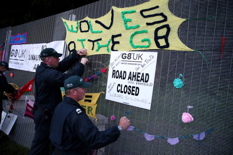 Police remove anti-G8 signs from the security fence at the G8 summit venue at Lough Erne on June 17, 2013 in Enniskillen, Northern Ireland. The two day G8 summit, hosted by UK Prime Minister David Cameron, is being held in Northern Ireland for the first time. (Peter Macdiarmid/Getty Images)