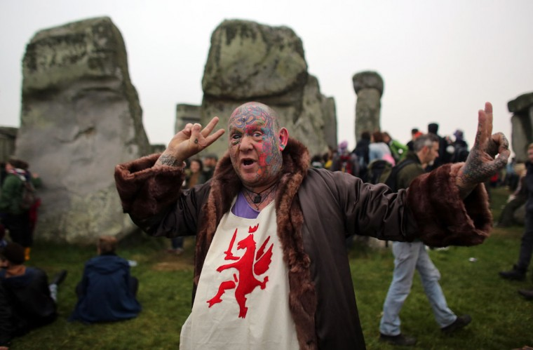 Solstice reveller Mad Al gestures as he joins druids, pagans and revellers celebrating the summer solstice at the megalithic monument of Stonehenge near Amesbury, England. Despite cloudy skies, thousands of revellers gathered at the 5,000 year old stone circle in Wiltshire to see the sunrise on the Summer Solstice dawn. The solstice sunrise marks the longest day of the year in the Northern Hemisphere. (Matt Cardy/Getty Images)