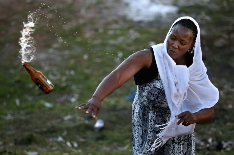 Members of the Indumiso Yamakholwa In Zion church throw glass bottles containing blessed water and a written prayer and smashing them to release the prayers to God during a ceremony in the Yeoville neighborhood in Johannesburg, South Africa. After being prayed over and blessed, worshipers will smash the bottles to release the prayers to God. The worn, arid space on top of the Yeoville hill offers worshipers of various Christian denominations from South African, Botswana, Zimbabwe, the Democratic Republic of Congo and other African nations an open-air space where they can publicly practice their faith with a scenic view of downtown Johannesburg. (Chip Somodevilla/Getty Images)