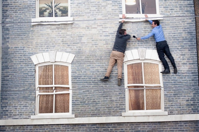 """People appear dangling at a large-scale installation art piece by Leandro Erlich, named """"Dalston House"""" on June 24, 2013 in London, England. Part of the """"Beyond Barbican"""" summer series, the interactive installation is a full facade of a late nineteenth-century Victorian terraced house built on the ground with a large mirror above it to reflect people as to appear dangling from the structure. (Dan Dennison/Getty Images)"""