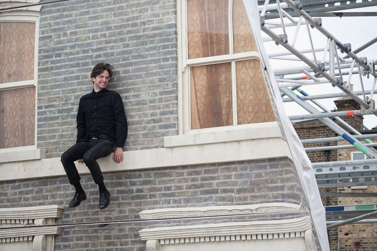 """A man interacts with a large-scale installation art piece by Leandro Erlich, named """"Dalston House,"""" displayed on June 24, 2013 in London, England. (Dan Dennison/Getty Images)"""