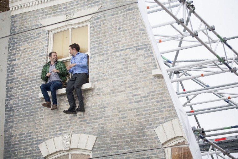 """Men appear in a window as a large-scale installation art piece by Leandro Erlich, named """"Dalston House,"""" is displayed on June 24, 2013 in London, England. (Dan Dennison/Getty Images)"""
