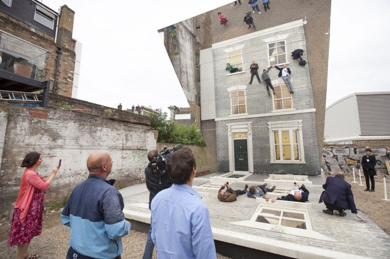 "People look on as a large-scale installation art piece by Leandro Erlich, named ""Dalston House,"" is displayed on June 24, 2013 in London, England. (Dan Dennison/Getty Images)"