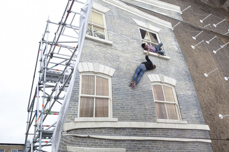 """A person appears to be dangling as a large-scale installation art piece by Leandro Erlich, named """"Dalston House,"""" is displayed on June 24, 2013 in London, England. (Dan Dennison/Getty Images)"""