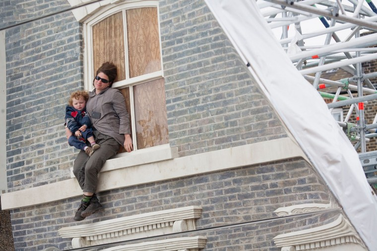 """A child and adult interact with a large-scale installation art piece by Leandro Erlich, named """"Dalston House,"""" is displayed on June 24, 2013 in London, England. (Dan Dennison/Getty Images)"""