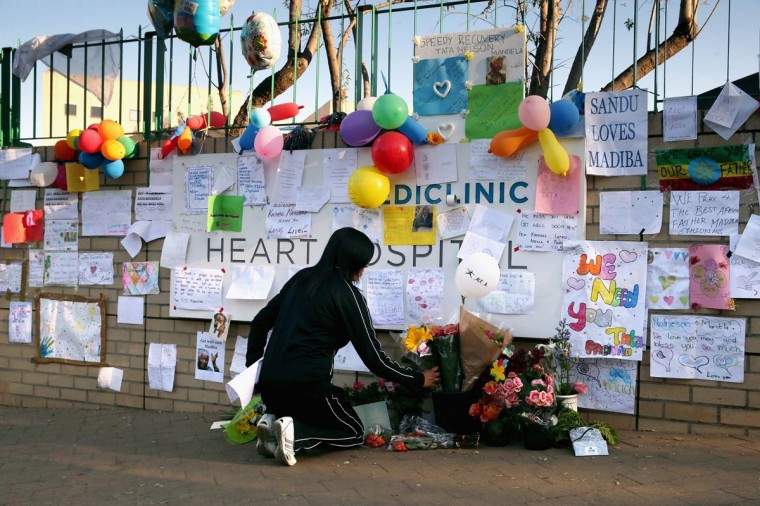 A woman places flowers at the base of the wall bearing dozens of hand-made messages of support for former South African President Nelson Mandela outside the Mediclinic Heart Hospital June 25, 2013 in Pretoria, South Africa. (Chip Somodevilla/Getty Images)