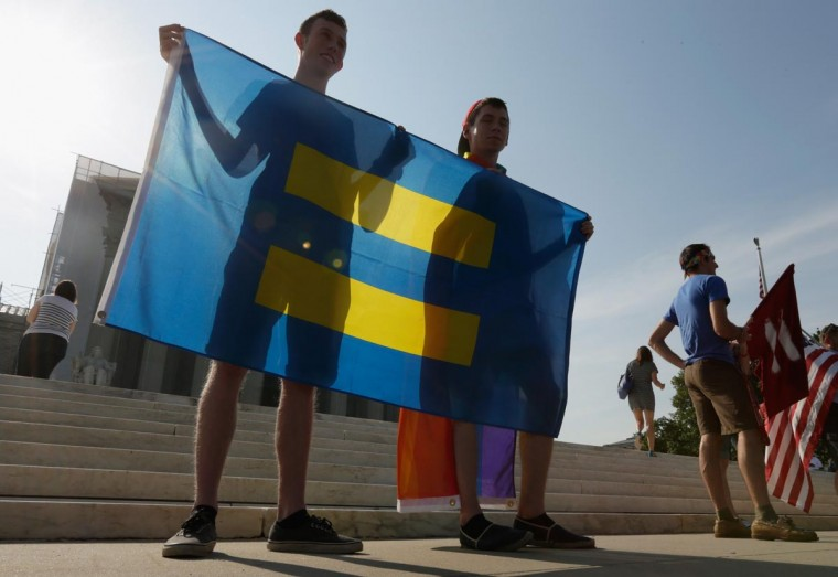 Gay rights supporters Brian Sprague (L) and Charlie Ferrusi, from Albany, New York, hold a Human Rights flag outside U.S. Supreme Court building on June 26, 2013 in Washington, DC. (Win McNamee/Getty Images)