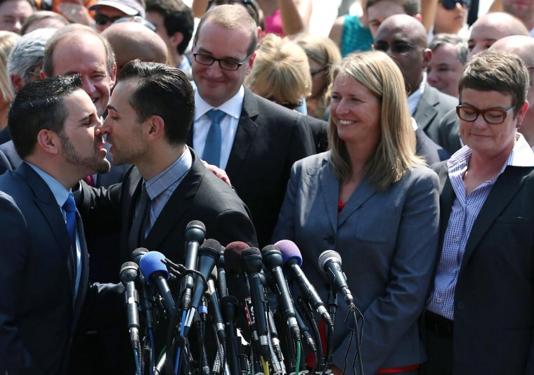 Plaintiff couples Paul Katami (L) kisses Jeff Zarillo (2nd L) while Sandy Steier (2nd R) Kris Perry stand nearby after the U.S. Supreme Court ruled that the Defense of Marriage Act (DOMA) is unconstitutional at the Supreme Court, June 26, 2013 in Washington, DC. (Mark Wilson/Getty Images)