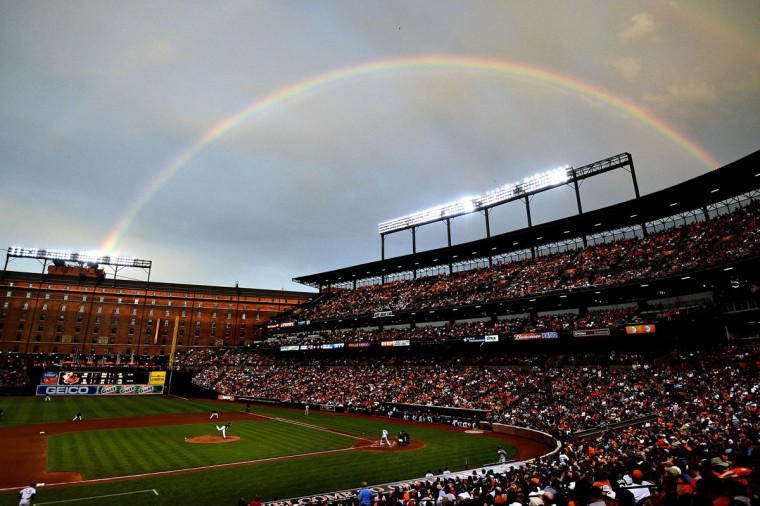 A rainbow shines in the sky as Orioles pitcher Kevin Gausman works Yankees batter Alberto Gonzalez at Oriole Park at Camden Yards on June 28, 2013 in Baltimore, Maryland. (Patrick Smith/Getty Images)