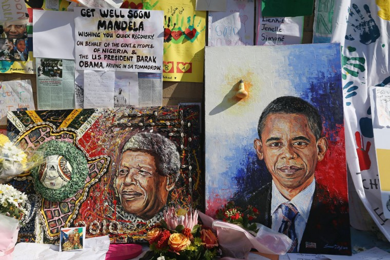 Images of Nelson Mandela and Barack Obama are depicted on a wall covered with messages and flowers outside the MediClinic Heart hospital on June 29, 2013 in Pretoria. U.S. President Barack Obama met with former South African leader Nelson Mandela's family to offer prayers as Mandela continues to be treated for a lung infection. (Dan Kitwood/Getty Images)