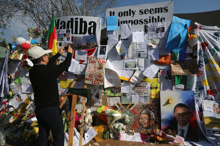 A wellwisher takes a picture of a wall covered with messages and flowers for former South African President Nelson Mandela outside the MediClinic Heart hospital on June 29, 2013 in Pretoria, South Africa. U.S. President Barack Obama met with the former South African leader's family to offer prayers as Mandela continues to be treated for a lung infection. (Dan Kitwood/Getty Images)