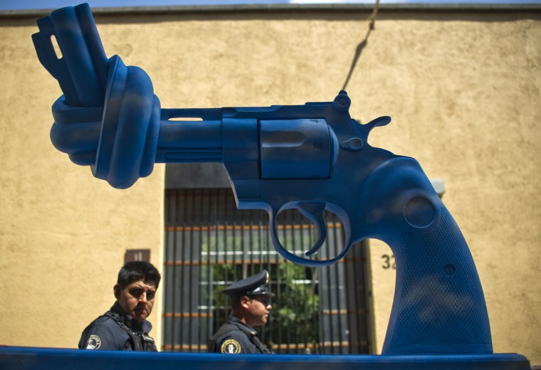 October 4, 2011: Two policemen walk by a knotted gun-shaped sculpture in Mexico City. Six giant guns with a tied barrel --to stop bullets-- including a replica of one made by Yoko Ono in memory of John Lennon, are on display in the capital within a campaign against drug-related violence, which has left more than 41,000 dead since December 2006. (Ronaldo Schemidt/AFP/Getty Images)