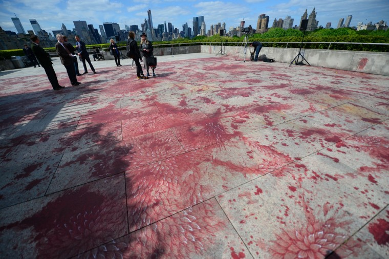 May 13, 2013: Visitors view Pakistani artist Imran Qureshi creation, painted on the rooftop of the Metropolitan Museum of Art, during a preview of the annual Met's Roof Garden commission, in New York. Qureshi, who uses the nearly 8,000-square-foot open-air space as his canvas, depicts his emotional response to violence occurring in Pakistan and across the globe, by working areas with blood-like spilled and splattered red acrylic paint into patterns of lush ornamental leaves that evoke the luxuriant walled gardens that are ubiquitous in miniatures of the Mughal court and also echo the foliage of Central Park surrounding the Roof Garden. Qureshi is the first artist to create a work that is be painted directly onto the roof's surface of the museum, encouraging visitors to walk on it as they view it. (Emmanuel Dunand/AFP/Getty Images)