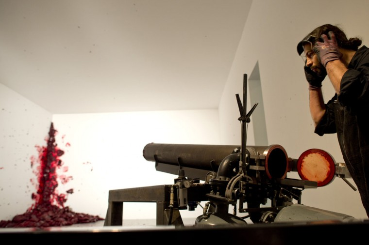 """May 17, 2013: A cannon operator adjusts his earmuffs while operating the installation """"Shooting into the corner"""" at the """"Kapoor in Berlin"""" exhibition at the Martin Gropius Bau museum in Berlin. (Odd Andersen/AFP/Getty Images)"""