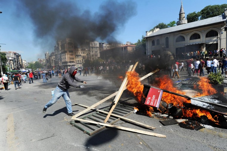 A man throws wood on a fire as Turkish protestors and riot policemen clash on June 1, 2013, during a protest against the demolition of Taksim Gezi Park, in Taksim Square in Istanbul. (Bulent Kilic/AFP/Getty Images)