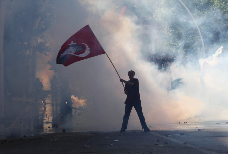Tear gas surrounds a protestor holding a Turkish flag with a portrait of the founder of modern Turkey Mustafa Kemal Ataturk as he takes part in a demonstration in support of protests in Istanbul and against the Turkish Prime Minister and his ruling Justice and Development Party (AKP), in Ankara, on June 1, 2013. (Adem Altan/AFP/Getty Images)