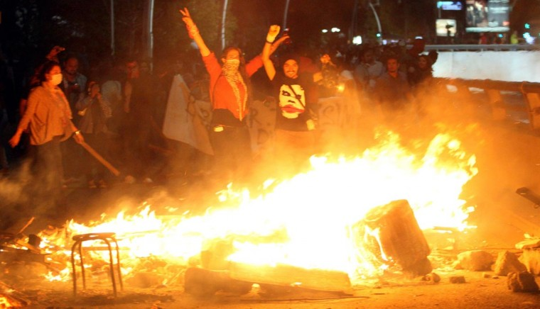 Anti-government protestors gesture as they stand next to objects set on fire during a demonstration in Ankara, early on June 3, 2013, in a nationwide wave of protests. (Adem Altan/AFP/Getty Images)
