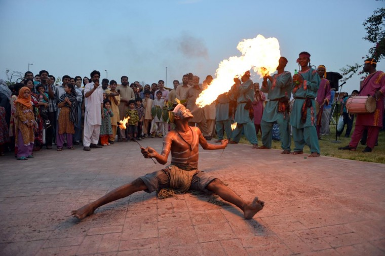A Pakistani folk artist breathes fire as he performs at the Margalla Festival 2013, which began at the Arts and Crafts Village in Islamabad on June 2, 2013. (Aamir Queshi/AFP/Getty Images)