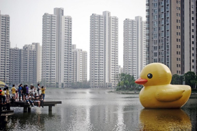This picture taken on June 1, 2013 shows visitors posing for photos before a yellow rubber duck floating on a lake in a community in eastern China's Tianjin. (Stringer/AFP/Getty Images)