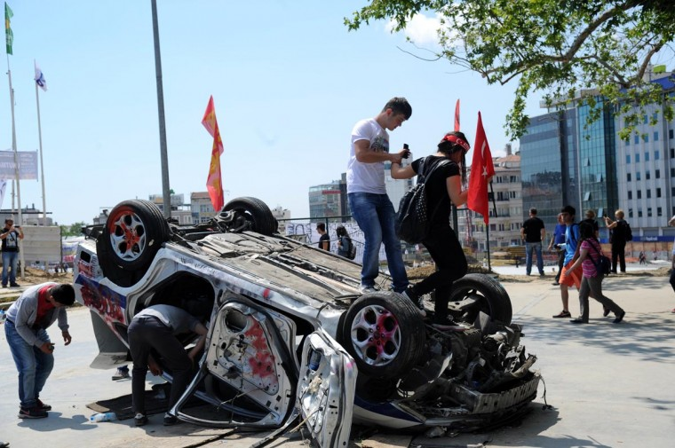 People walk on an overturned police car on Taksim square in Istanbul on June 3, 2013 after days of protests against the demolition of Gezi park. (Bulent Kilic/AFP/Getty Images)