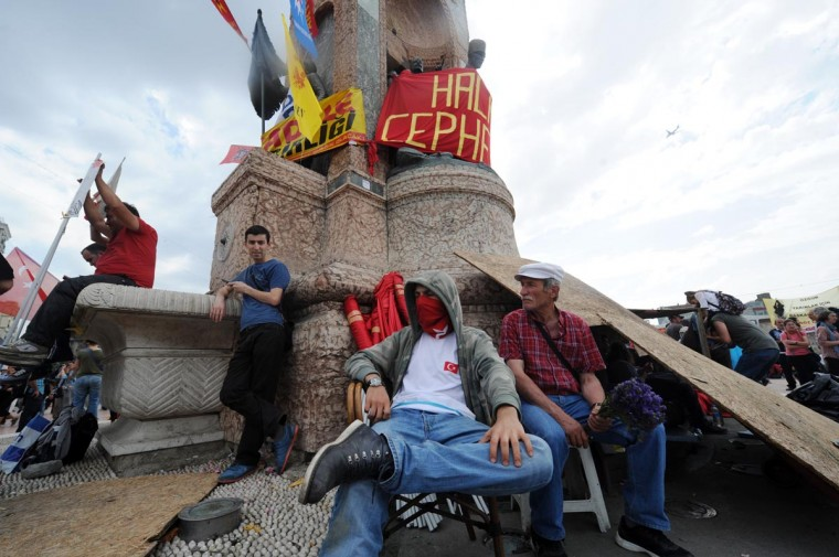 Protestors sit under the Republic monument on Taksim square in Istanbul on June 3, 2013 after days of protests against the demolition of Gezi park. (Bulent Kilic/AFP/Getty Images)