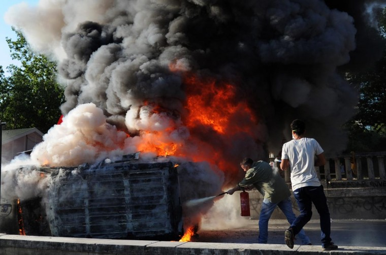 Two men try to put out a fire on a Police car set alite on Taksim square in Istanbul on June 3, 2013 during protests against the Islamic-rooted government. (Bulent Kilic/AFP/Getty Images)