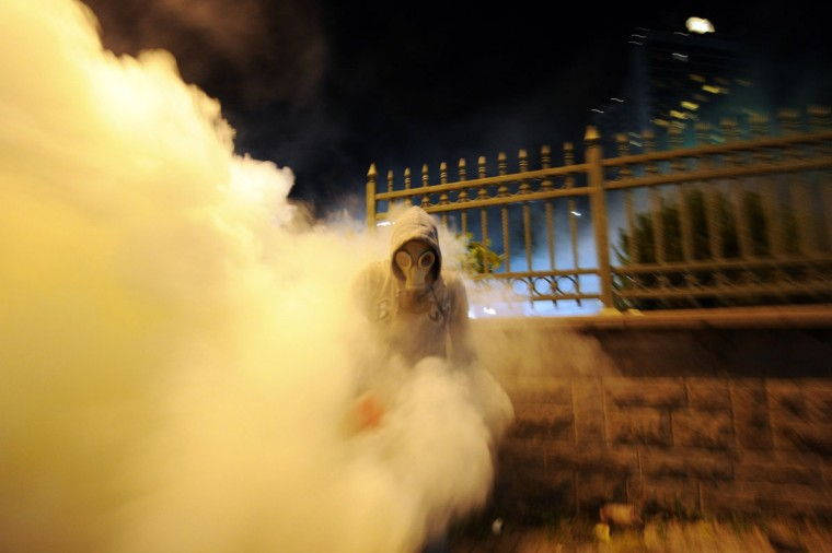 A protestor runs away from tear gas during clashes with Turkish riot policemen between Taksim and Besiktas in Istanbul on June 3, 2013 during a demonstration against the demolition of the park. (Bulent Kilic/AFP/Getty Images)