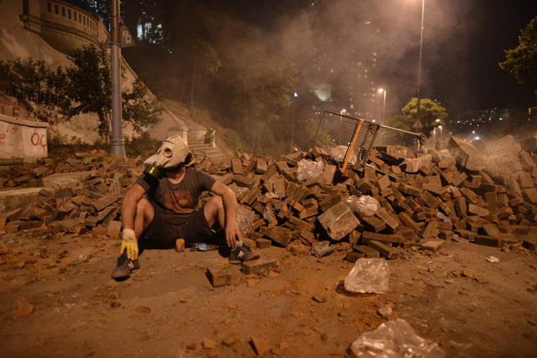 A demonstrator takes cover at a road block between Taksim and Besiktas in Istanbul on June 4, 2013 during a demonstration against the demolition of the park. (Aris Messinis/AFP/Getty Images)