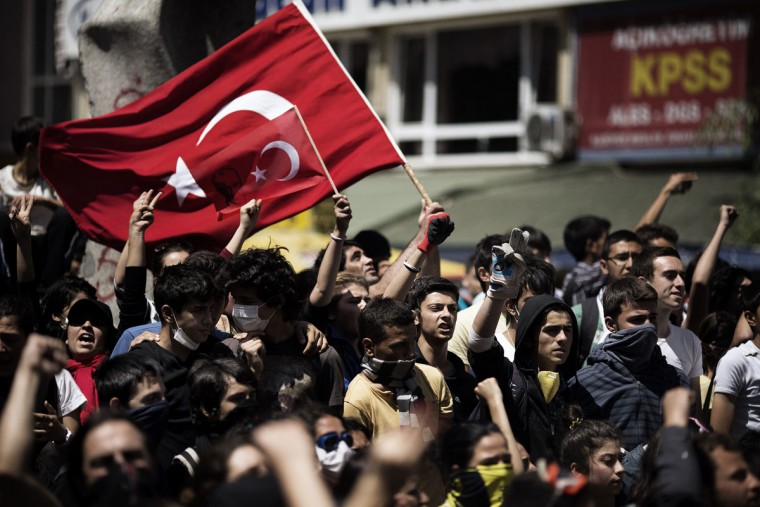 """Turkish demonstrators hold their national flag on June 4, 2013 during a protest in front of the prime minister's office in Ankara. Turkey's Islamic-rooted government said on June 4 it had """"learnt its lesson"""" and appealed for an end to mass street protests. (Marco Longari/AFP/Getty Images)"""