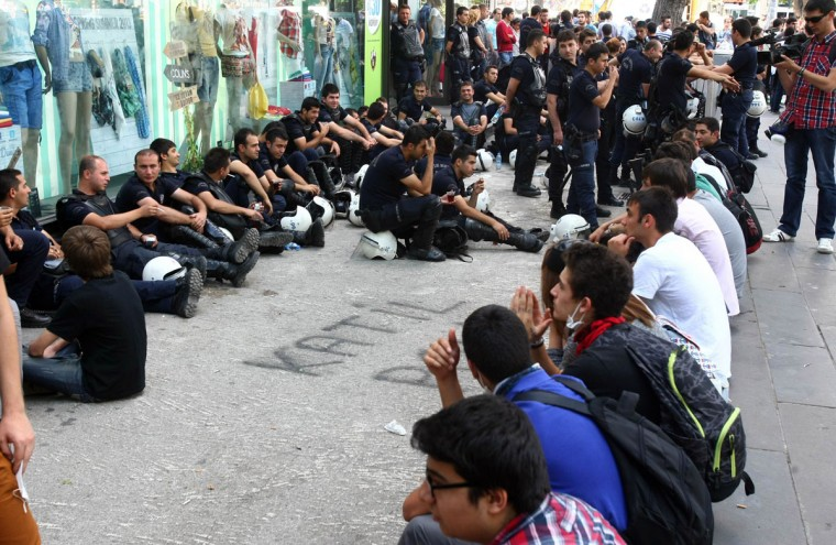 """Demonstrators sit in front of policemen resting during a demonstration in Ankara on June 4, 2013. Turkey's Islamic-rooted government said Tuesday it had """"learnt its lesson"""" and appealed for an end to mass street protests. The United Nations joined Washington in pressing for a full investigation into allegations of excessive use of police force against anti-government demonstrators while Turkey's main union federation launched a two-day strike over what it branded """"state terror"""". (Adem Altan/AFP/Getty Images)"""