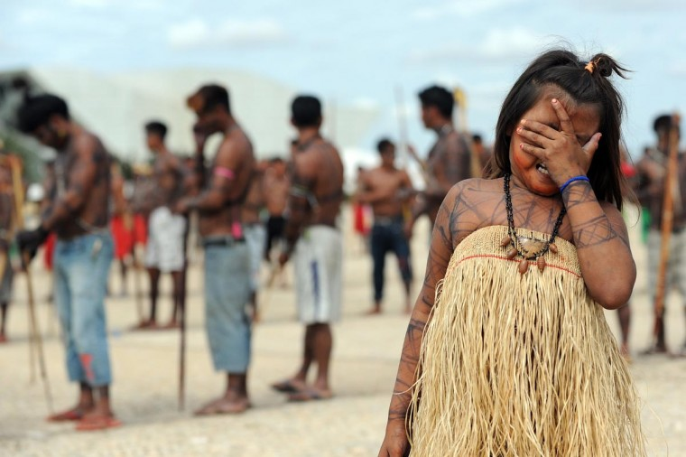 Munduruku natives rally in front of the Planalto Palace in Brasilia, on June 6, 2013. Five indigenous tribes are calling for legislation under which they would have to be consulted prior to any official decision affecting them with respect to the dam's construction. Belo Monte, which is being built at a cost of $13 billion, is expected to flood an area of 500 square km along the Xingu River, displacing 16,000 people, according to the government. Some NGOs have estimated that some 40,000 people would be displaced by the massive project. Indigenous groups say the dam will harm their way of life while environmentalists warn of deforestation, greenhouse gas emissions and irreparable damage to the ecosystem. (Evaristo Sa/AFP/Getty Images)