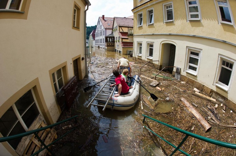 People in a rubber boat make their way through the floods of the river Elbe submerging houses in the city of Stadt Wehlen, eastern Germany, on June 7, 2013. Central Europe's worst floods in over a decade claimed a 12th victim on June 6, 2013 as torrents of muddy water surged down swollen rivers through the Czech Republic and Germany, flooding villages, threatening cities and forcing mass evacuations. (Arno Burgi/AFP/Getty Images)