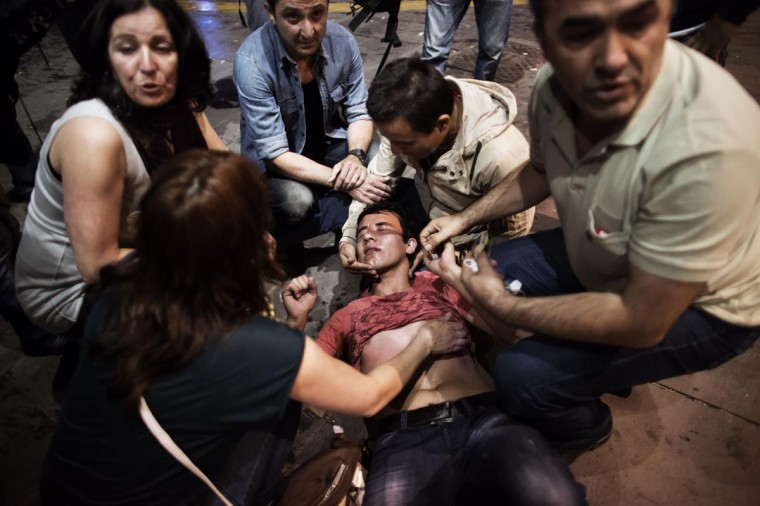 A beaten and shocked demonstrator is helped by other protesters on June 9, 2013 after being confronted by riot police on Kizilay square in Ankara in Turkey. (Marco Longari/AFP/Getty Images)
