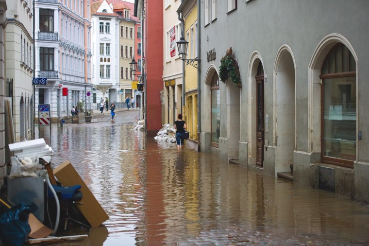 A woman walks through a flooded street in Meissen after the River Elbe causing massive flooding in the area on June 9, 2013. Parts of northern Germany continued to be threatened by the swollen River Elbe where a dyke was breached overnight in Saxony-Anhalt state, adding hundreds to the already thousands of German residents to have been evacuated. (Arno Burgi/AFP/Getty Images)