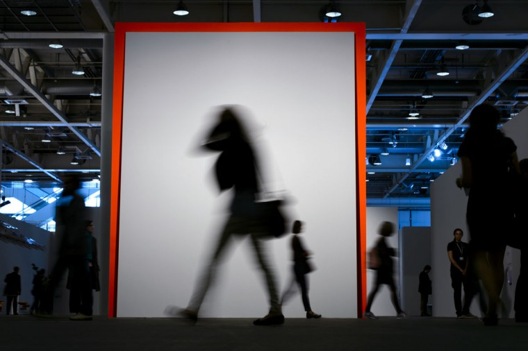 "A visitor walk past on June 11, 2013 an artwork by Matt Connors entitled ""Demonstration (red and blue)"" during the preview day of Art Basel. (Fabrice Coffrini/AFP/Getty Images)"