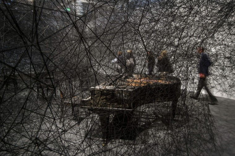 "Visitor watches on June 11, 2013 an artwork by Japanese artist Chiharu Shiota entitled ""In Silence"" during the preview day of Art Basel. (Fabrice Coffrini/AFP/Getty Images)"