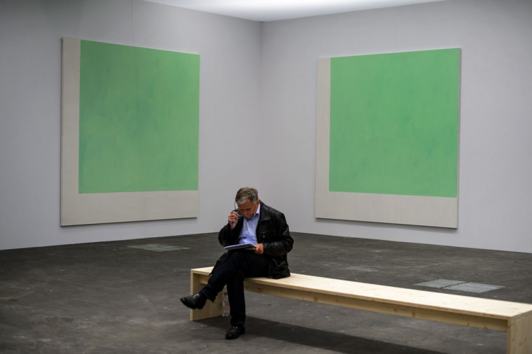 "A visitor reads on June 11, 2013 in front of an artwork by Guenther Foerg, entitled ""Untitled,"" during a preview day for the Art Basel 2013. (Fabrice Coffrini/AFP/Getty Images)"