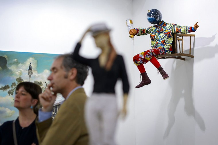 "Visitors look on June 11, 2013 at artwork in front of a sculpture by British-Nigerian artist Yinka Shonibare entitled ""Champagne Kid (Perching)"" during a preview day for the Art Basel 2013. (Fabrice Coffrini/AFP/Getty Images)"