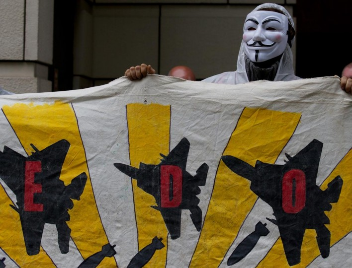 A demonstrator from 'Stop G8' displays a banner outside the offices of BAE Systems in London, on June 12, 2013, during a protest ahead of the G8 Summit. (Andrew Cowie/AFP/Getty Images)