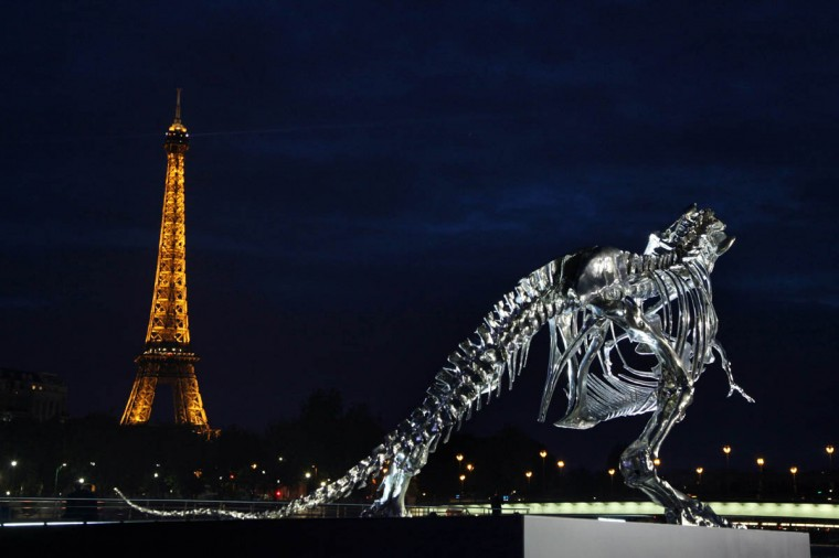 A giant chrome brushed aluminium skeleton of a Tyrannosaurus (T-Rex) dinosaur (Right), made by French sculptor and painter Philippe Pasqua, stands at the pier of riverboat company Bateaux-Mouches in Paris, with the Eiffel tower in the background (Left). (Claire Lebertre/Getty Images)