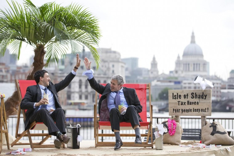 """Protestors dressed as a businessman give each other """"high five"""" on a protest site named by participants as the """"Isle of Shady Tax Haven"""" in London on June 14, 2013, ahead of the G8 Summit. Campaigners are calling for a crackdown on tax havens. (Justin Tallis/AFP/Getty Images)"""