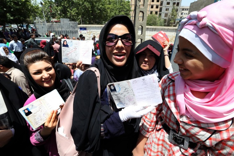 Iranian women show their documents as they queue to vote in the first round of the presidential election at a polling station in Tehran on June 14, 2013. (Atta Kanare/AFP/Getty Images)