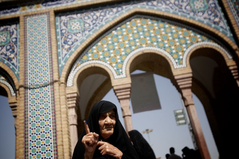 "An Iranian elderly lady raises up her ink-stained finger after voting in the first round of the presidential election at a polling station in Shah Abdolazim mausoleum, in southern Tehran. The 10-hour voting period in Iran's presidential election is to be extended because of a ""rush of voters,"" Interior Minister Mostafa Moammad Najar said. (Behrouz Mehri/AFP/Getty Images)"