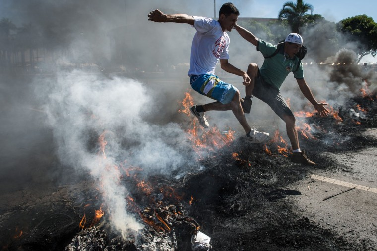 People jump over burnt tyres during a protest blocking the access to Brasilia's Mane Garrincha, one of the six host stadiums for the upcoming Confederations Cup, in Brasil. People demonstrate against the government's policy of the expenditure for the 2014 FIFA World Cup. A police spokesman said the protest was organized by the Homeless Workers Movement (MTST) which is campaigning to reduce Brazil's housing shortage by staging squatters' occupations in abandoned government buildings. (Yasuyoshi Chiba/AFP/Getty Images)